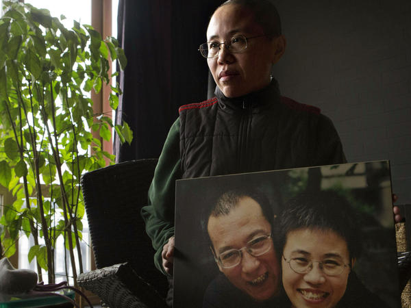 Liu Xia held a photo of herself and her husband during an interview at her home in Beijing in December 2012.