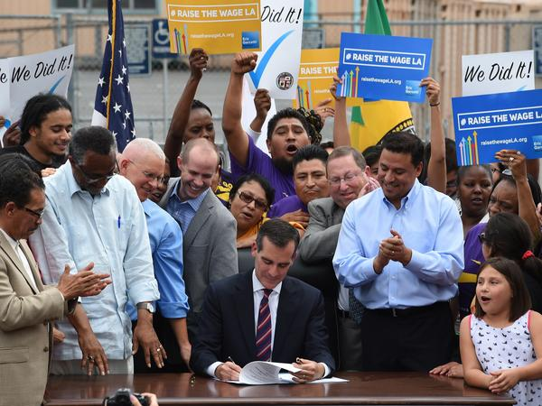 In 2015, Los Angeles Mayor Eric Garcetti (center) signs into law an ordinance raising the city's minimum wage to $15 an hour by 2020. Though California isn't one of them, 27 states have passed laws requiring cities to abide by state minimums.