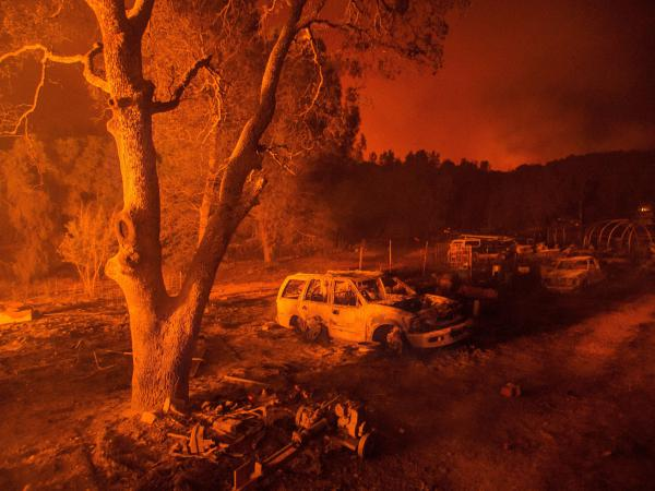 Fire illuminates the remains of a burned-out property near Mariposa, Calif., on Tuesday.