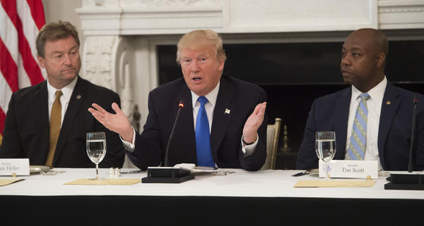 President Trump speaks alongside Republican Sens. Dean Heller of Nevada (left) and Tim Scott of South Carolina during a meeting with lawmakers to discuss the health care bill  on Wednesday.
