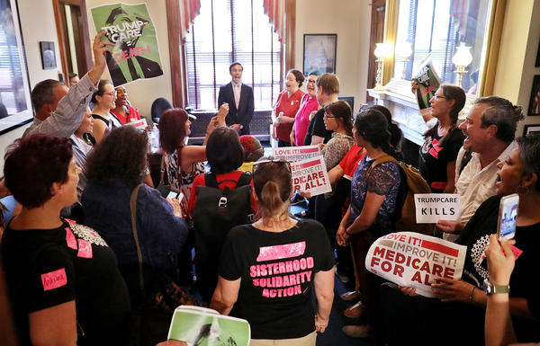 Dozens of people stand in the offices of Sen. Marco Rubio, R-Fla., protesting against the Republican health care plan on Capitol Hill on Thursday. Uncertainty about the future of the health care system has shaken insurers.