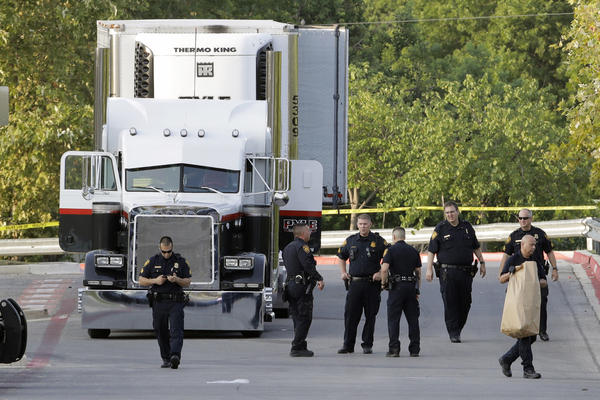 San Antonio police officers investigate the scene where eight people were found dead in a tractor-trailer loaded with at least 30 others outside a Walmart store in stifling summer heat in what police are calling a horrific human trafficking case, Sunday, July 23, 2017, in San Antonio. (Eric Gay/AP)