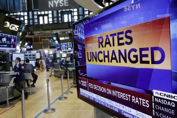 A television screen on the floor of the New York Stock Exchange shows the Federal Reserve's rate decision on Wednesday.