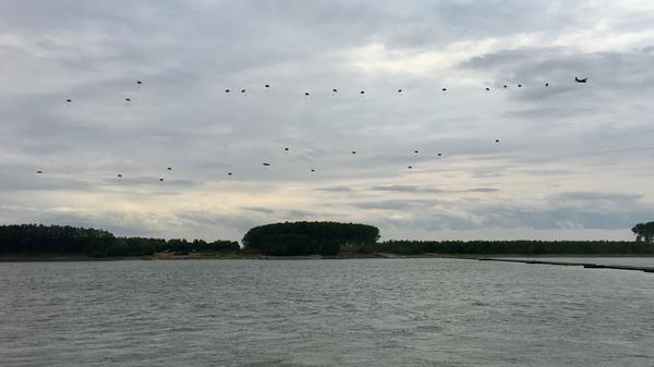 Romanian paratroopers drop from a C-130 transport to a bank of the Danube River.