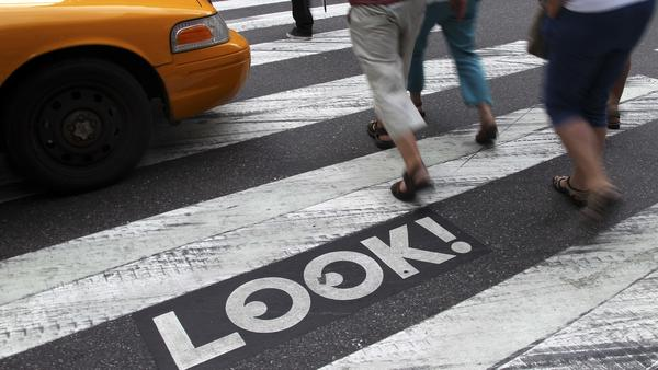 "Pedestrians walk past a ""Look!"" sign on the crosswalk at the intersection of 42nd Street and Second Avenue in New York. Cities all over the country are looking for ways to get pedestrians to pay more attention."