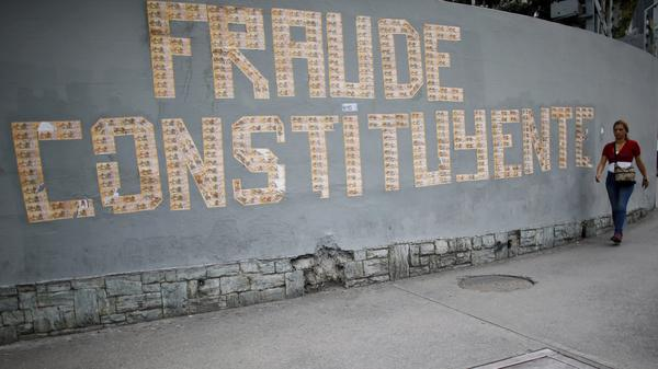 """A pedestrian walks next to a message on a wall formed with Venezuelan currency that reads in Spanish: """"The Constituent Assembly is a fraud"""", in Caracas, Venezuela, on Monday."""