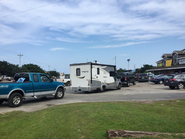 Vehicles line up at a gas station on Thursday on Ocracoke Island on North Carolina's Outer Banks, as visitors leave the island following a widespread power outage.