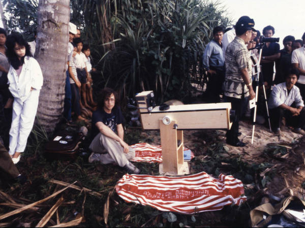 "Astronomer Glenn Schneider (center) was on the coast of Bangka Island, Indonesia, on March 18, 1988, preparing to observe and photograph that day's total solar eclipse using his ""disposable"" telescopic eclipse camera."