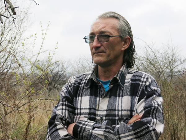 Oleg Kovalenko, 44, was injured on his left shoulder when a shell exploded overhead on the evening of April 5 while he and a neighbor were smoking cigarettes and drinking beers outside his fence. He says he can't afford to leave or repair his property, which is pockmarked from three years of shrapnel and bullets.