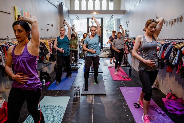 Women work on strengthening their core abdominal muscles in Leah Keller's exercise class for new moms, inside a San Francisco clothing store called Monkei Miles.
