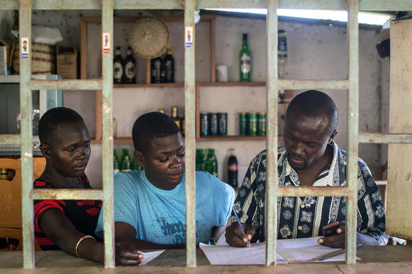 Otieno and two waitresses go over the accounts at his lakeside bar. To start the business he had to take out a loan. Now the payments are crushing him.