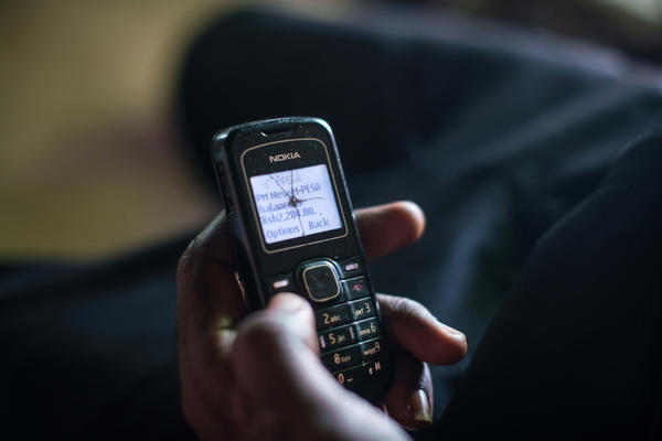 Dancan Odero checks his phone to confirm that the GiveDirectly transfer has been made.