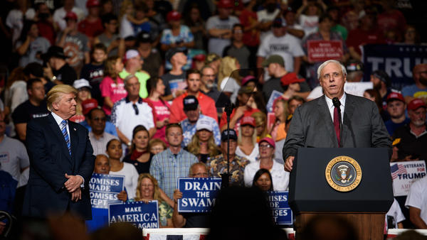West Virginia Gov. Jim Justice announces that he is switching parties to become a Republican as President Trump listens on at a campaign rally Thursday in Huntington, W.Va.
