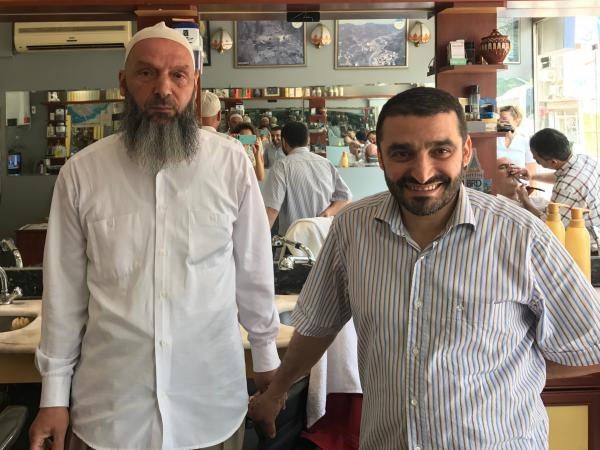 Suat Keceli, left, a retired stockroom worker, and his barber Yasar Ayhan pose in Ayhan's barber shop in Kasimpasa, the Istanbul neighborhood where President Recep Tayyip Erdoğan grew up. Keceli is a conservative Muslim who kept his daughter out of school when headscarves were banned in the classroom.