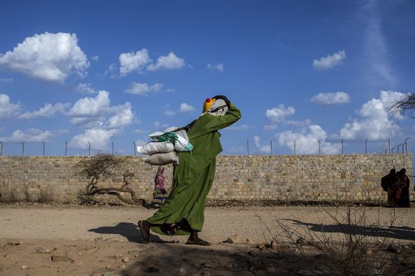 A woman carries bags of food on her back at Dakamur camp, Somalia, in March.