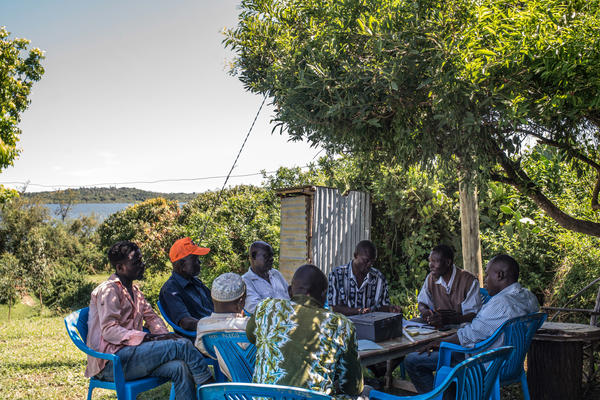 Denis Otieno (third from the right) meets with fellow members of the savings club that he founded after GiveDirectly began providing every adult in the village with monthly cash aid.