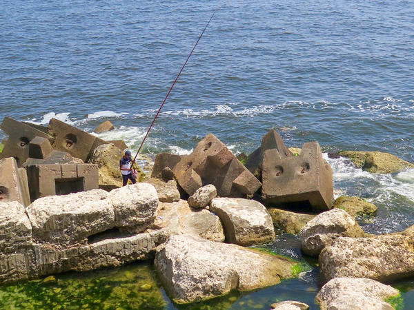 A fisherman stands on what are believed to be remains of the ancient lighthouse of Alexandria — considered one of the Seven Wonders of the ancient world.