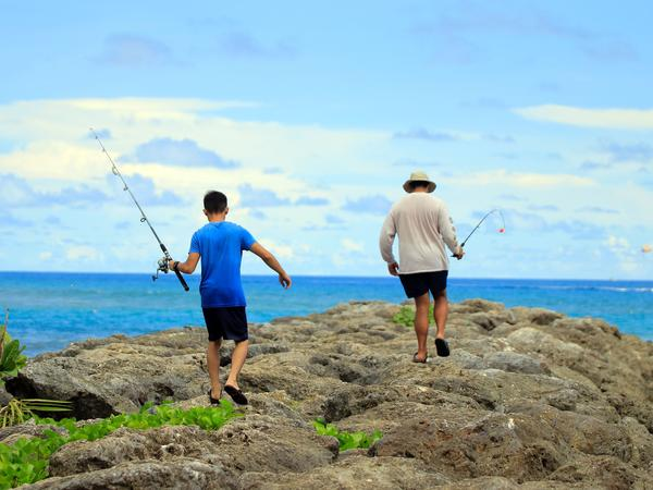 Residents go fishing this week near Tumon Beach in Guam. Some people on the strategically located island fear the president's rhetoric has exposed them to danger.