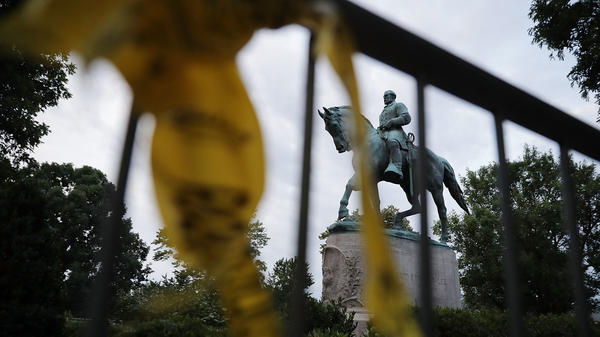 """The statue of Confederate Gen. Robert E. Lee stands in the center of Emancipation Park the day after violence broke out in Charlottesville, Va. The """"Unite the Right"""" rally aimed to save the statue, which the city council has voted to remove. But several cities have now reacted to the rally by hastening the removal of their own Confederate monuments."""
