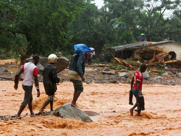 Residents pass a damaged building as they walk through floodwaters on the outskirts of Sierra Leone's capital, Freetown, on Monday.