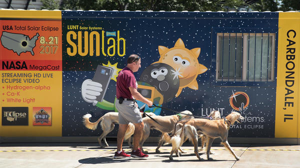 Jim Blair walks Saluki dogs past a solar eclipse exhibit on the campus of Southern Illinois University in Carbondale, Ill. With approximately 2 minutes 40 seconds of totality the area in Southern Illinois will experience the longest duration of totality during the eclipse on August 21.