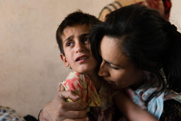Reihana, 28, comforts her son after she punished him out of despair. She was 14 when she was sold by her father to a man twice her age. She was physically and sexually abused until she ran away to Kabul with her five children. She now studies at a university part time and works full time at Afghanistan's anti-narcotics ministry.