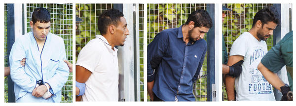 Four men —Mohamed Houli Chemlal (from left), Driss Oukabir, Salah El Karib and Mohamed Aallaa — suspected of being part of a terror cell accused of killing 15 people in attacks in Spain leaves a Civil Guard base on the outskirts of Madrid prior to their court appearance on Tuesday.