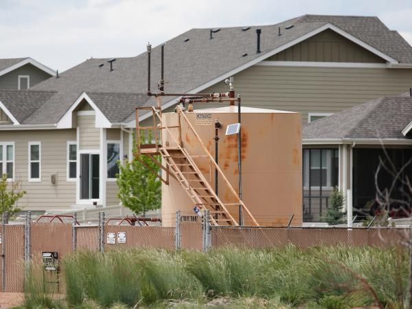 An oil storage tank sits by a housing development off state highway 119 near Firestone, Colo.