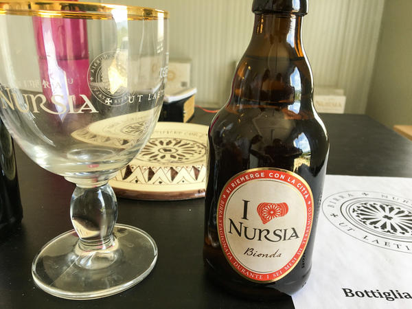 "A bottle of Nursia ""quake"" beer includes a special logo showing the basilica's damaged rose window."