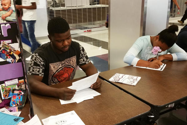 Derius Matthews, 17, fills out forms on registration day. He says he's ready for his senior year — and Thorton High's football season — to start.