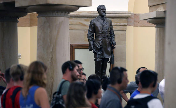Tourists walk past the statue of Confederate Gen. Robert E. Lee inside the U.S. Capitol on Aug. 17. House Minority Leader Nancy Pelosi, D-Calif., has called for the removal of all Confederate statues from the Capitol building.