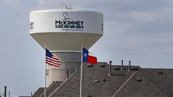A water tower with a city slogan painted across it is seen behind a housing area in McKinney, Texas, in 2015.
