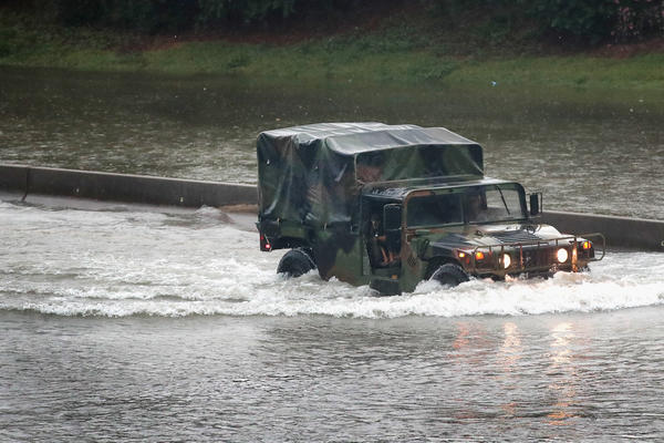 A military truck navigates along Interstate 10, which has been inundated. Harvey is expected to dump upwards of 40 inches of rain in Texas over the next couple of days.