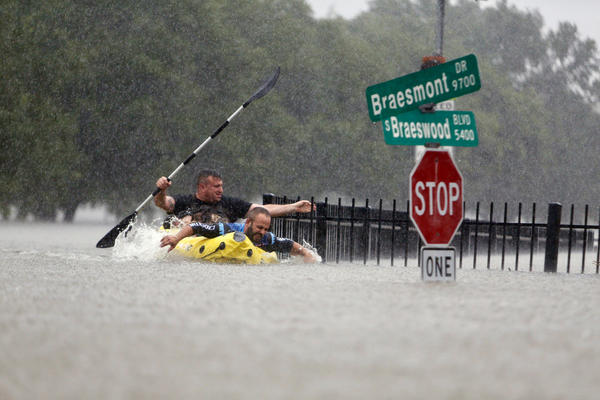 Two kayakers try to beat the current pushing them down an overflowing Brays Bayou along S. Braeswood in Houston, on Sunday. Rescuers answered hundreds of calls for help Sunday as floodwaters from the remnants of Hurricane Harvey climbed high enough to begin filling second-story homes, and authorities urged stranded families to seek refuge on their rooftops