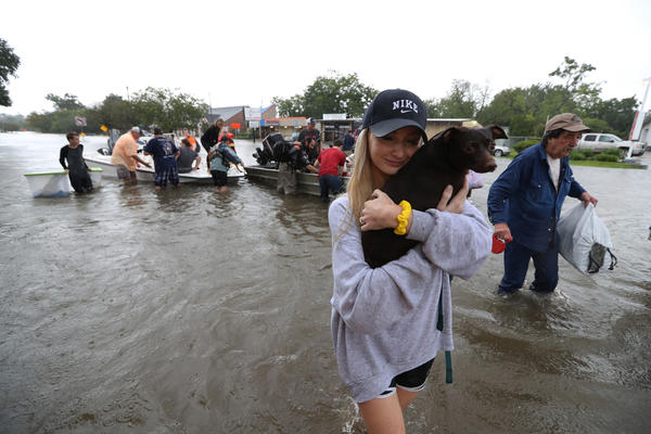 Mikhail Bachynsky hugs her dog Lily after they were rescued from their home on Sunday in the Friendswood area of Houston.