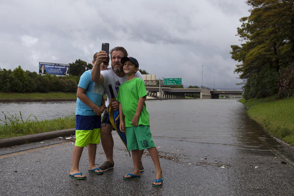 Paul Lenz (center), and his children Graham, 9 (left), and Miles, 7, photograph the flooding on I-10 in Houston.