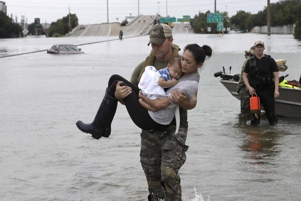 Houston Police SWAT officer Daryl Hudeck carries Catherine Pham and her 13-month-old son Aiden after rescuing them from their home surrounded by floodwaters from Tropical Storm Harvey in Houston on Sunday. The remnants of Hurricane Harvey sent devastating floods pouring into Houston Sunday as rising water chased thousands of people to rooftops or higher ground.