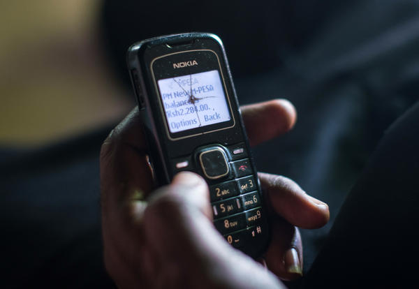 A recipient of cash aid through GiveDirectly's experiment checks his phone to confirm that the latest monthly transfer has been made.