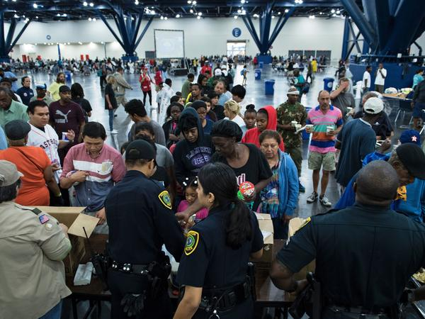 Flood victims gather for food at a shelter in the George R. Brown Convention Center on Monday in Houston.