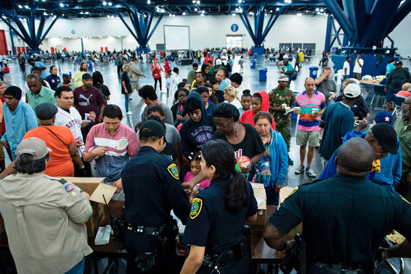 People gather for food at a shelter in the convention center. Flooding unleashed by monster storm Harvey left Houston, the fourth-largest city in the United States, increasingly isolated as its airports and highways shut down and residents fled homes waist-deep in water.