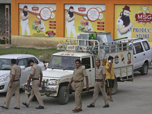 Indian policemen walk in front of a store belonging to Dera Sacha Sauda sect chief Gurmeet Ram Rahim Singh after it was sealed by authorities, near Sonipat, India, on Saturday. Security forces patrolled the streets of the north Indian state of Haryana, where mobs went on a rampage after a court declared Singh guilty of raping two of his followers.