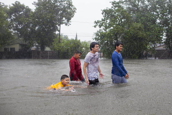 Kids walk — and swim — in the floodwaters in a Houston neighborhood as the rain continues to pour down.