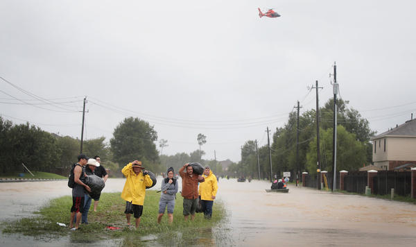 People make their way out of a neighborhood flooded by Tropical Storm Harvey in Houston on Monday. Trump did not visit Houston so he won't complicate relief efforts.