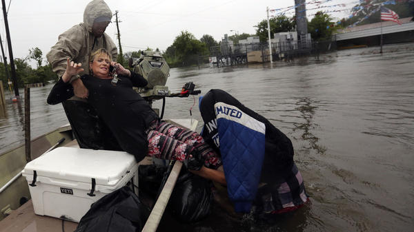 Rhonda Worthington is lifted into a boat while on her cellphone with a 911 dispatcher on Monday in Houston. Houston and other areas along the Gulf Coast are facing intense flooding from Tropical Storm Harvey.