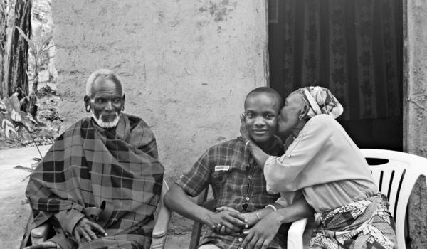 Ndosi (center) rents rooms in his family home. Sometimes he takes guests to visit relatives like his aunt and uncle (pictured above).