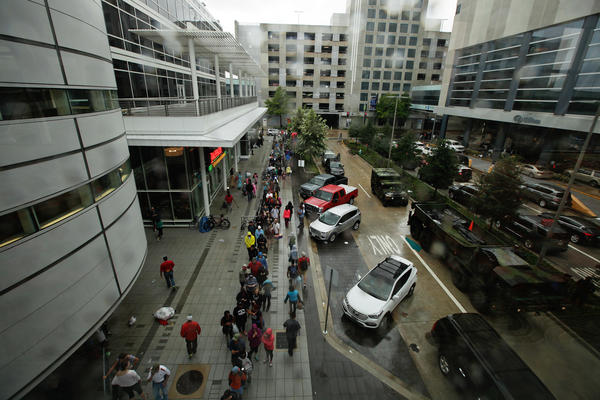 Lines of people wait outside the George R. Brown Convention Center, which has been turned into a shelter for people seeking refuge from Tropical Storm Harvey, in downtown Houston.