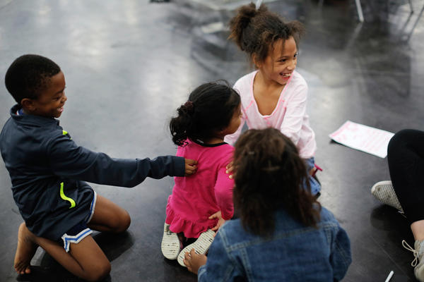 Erica Brown's children, JaCorey Landheart, 7 (left), Jazmine Brown, 8 (top right), and Cal'Rhyanna Brown, 6 (foreground), play with another girl at the convention center.