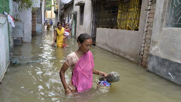 Residents walk through floodwaters in Malda, West Bengal, India, on Thursday. The death toll from floods sweeping South Asia has climbed above 1,000, according to news services tracking official tallies.