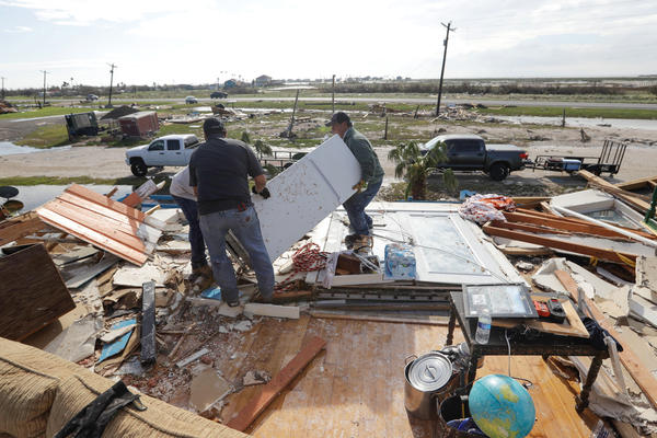 Lupe Tijerina, (left) and Andy Guerra and Felix Tijerina work to salvage items from their family home that was destroyed in the wake of Hurricane Harvey, in Rockport, Texas on Tuesday.