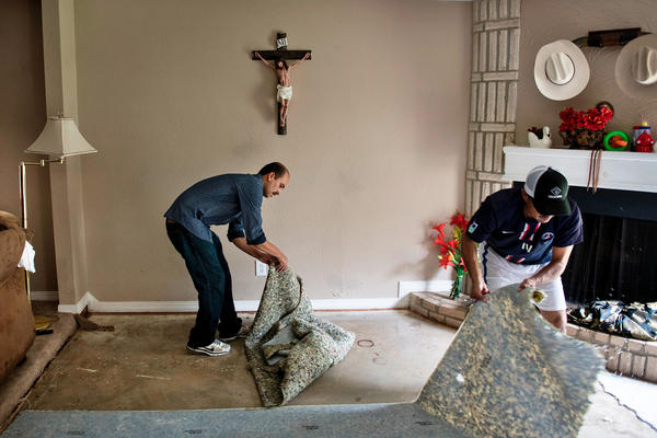People tear out carpet from a flood-damaged home after waters receded during the aftermath of Hurricane Harvey in Houston, Texas.